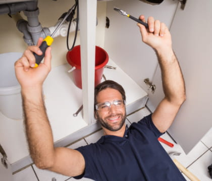 man smiling while working under a sink